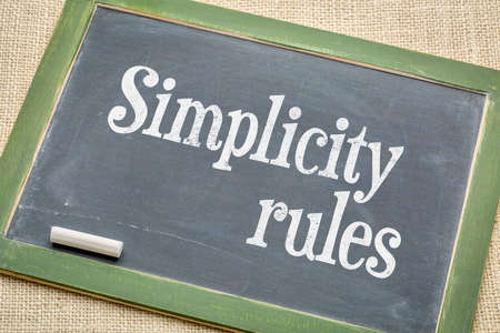 simplicity rules sign - white chalk text on a vintage slate blackboard  against burlap canvas Stock Photo