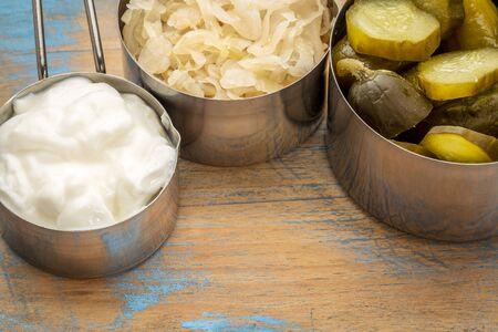 yogur: chucrut, encurtidos de pepino y yogur - populares alimento fermentado probiótico - tres tazas de medir contra la madera rústica Foto de archivo