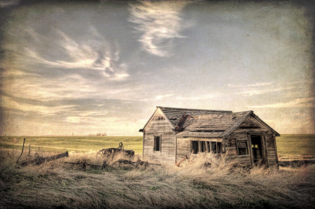 homestead: old abandoned house and farming machinery on Colorado prairie with texture effect finish Stock Photo