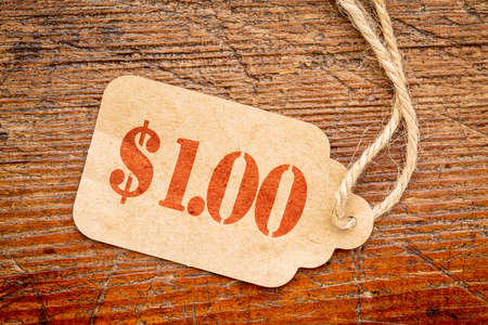 one dollar: one dollar price tag  price tag against a rustic barn wood - sale marketing concept