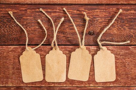 price tag: four blank paper price tags with a twine against a rustic scratched wood
