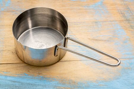cooking utensil: empty metal measuring scoop (12 cup) against painted wood