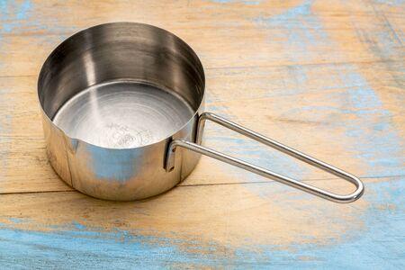 painted wood: empty metal measuring scoop (12 cup) against painted wood