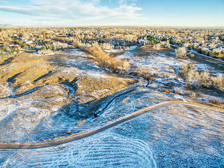 bike trail: aerial view of Colorado foothills with a bike trail over prairie in winter or late fall scenery Stock Photo