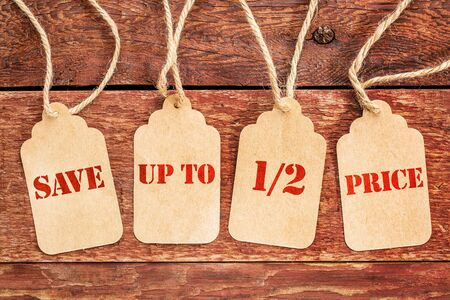 half price: save up to half price banner  - sign on paper price tags against a rustic barn wood