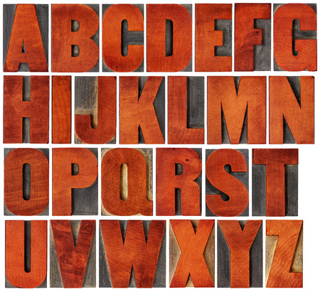 letterpress letters: complete English alphabet set - a collage of 26 isolated vintage wood letterpress printing blocks, scratched and stained by red ink , gothic bold extended font Stock Photo