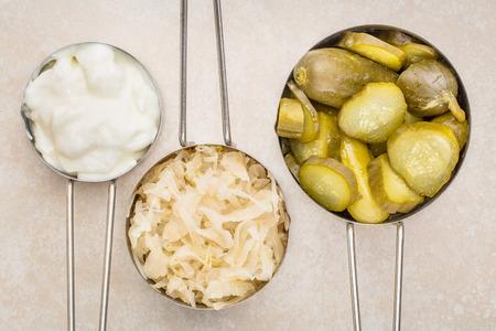 zuurkool, komkommer augurken en yoghurt - populaire probiotische gefermenteerde levensmiddelen - drie maatbekers tegen keramische tegels Stockfoto
