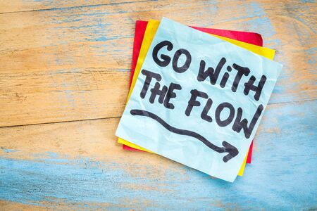 Go with the flow advice or reminder on a sticky note against grunge painted wood