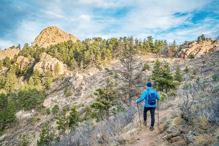 horsetooth rock: mail hiker with a backpack on a trail to Horsetooth Rock, a landmark of Fort Collins, Colorado, winter scenery without snow