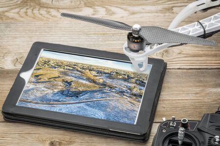 fort collins: drone aerial photography concept - reviewing aerial picture of Colorado foothills near Fort Collins on a digital tablet with a drone rotor and radio control transmitter, winter scenery
