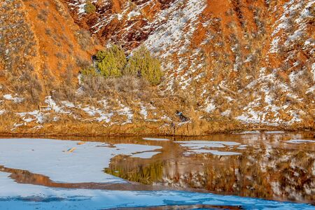 red mountain open space: water, snow, ice and red hills  - winter scenery in Red Mountain Open Space near Fort Collins, Colorado Stock Photo
