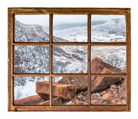 sash: sandstone rocks and a mountain valley in fog and snow  as seen  through vintage, grunge, sash window with dirty glass - travel or vacation concept