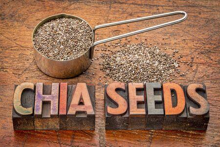 semilla: las semillas de chía en una cuchara de metal de medición y un texto en bloques de impresión tipográfica cosecha de madera rústica contra