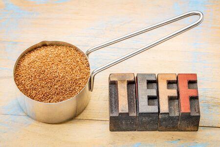 wood type: gluten free teff grain in a metal measuring scoop with a text in vintage letterpress wood type blocks Stock Photo
