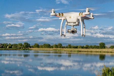 phantom: FORT COLLINS, CO, USA, SEPTEMBER 7 , 2015:  DJI  Phantom 3 quadcopter drone flying with a camera over a lake.