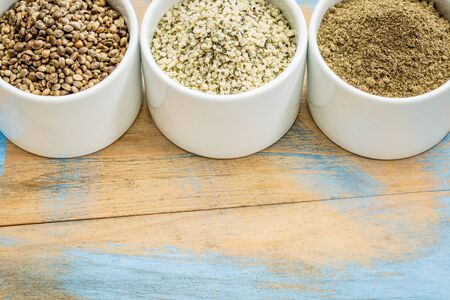 hemp hemp seed: hemp products: seeds, hearts (shelled seeds) and protein powder in small ceramic bowls on a grunge wood with a copy space Stock Photo