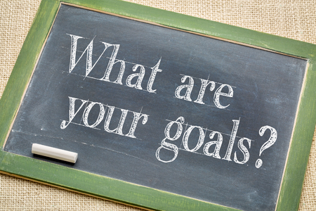 goal setting: What are your goals? A question on a vintage slate blackboard with a white chalk against burlap canvas