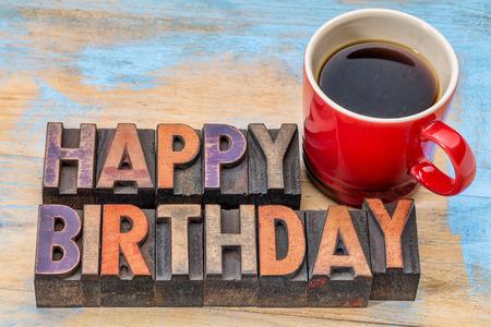 felicitaciones cumpleaÑos: Tarjeta de felicitación feliz cumpleaños - texto en el tipo de madera de cosecha con una taza de café