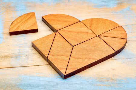 brainteaser: heart version of tangram, a traditional Chinese Puzzle Game made of different wood parts to build abstract figures from them, painted wood background