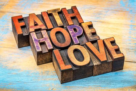 letterpress words: faith, hope and love - a collage of words in vintage letterpress wood type stained by color inks against painted wood