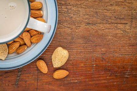 a cup of almond milk with almond nuts on a rustic wood table with a copy space