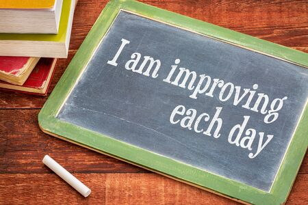affirmation: I am improving each day - self development concept or positive affirmation on a  slate blackboard with a white chalk and a stack of books against rustic wooden table