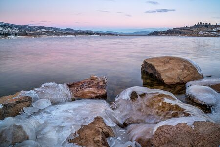 water frozen: winter dawn over icy shores of Horsetooth Reservoir near Fort Collins in northern Colorado