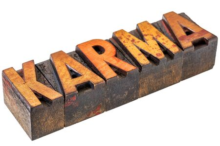 wood type: karma word abstract  - an isolated banner in vintage letterpress wood type stained by color inks Stock Photo