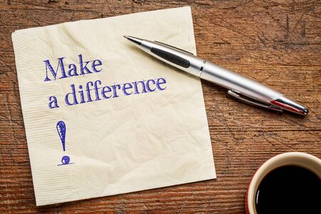 difference: Make a difference! A motivational  text on a napkin with a cup of coffee