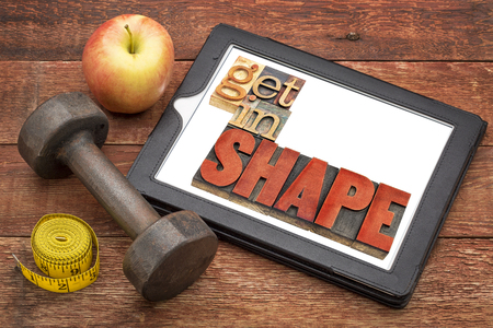 fitness motivation: get in shape motivation fitness concept - text  in vintage letterpress wood type on a digital tablet, with a dumbbell, apple and tape measure Stock Photo