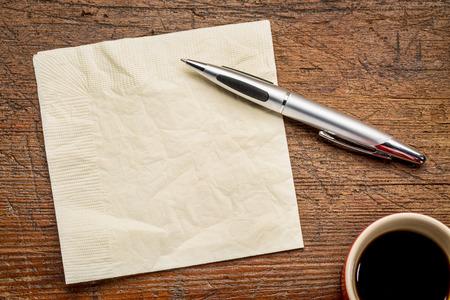 servilleta, la pluma y el café sobre la mesa de madera del grunge, vista desde arriba