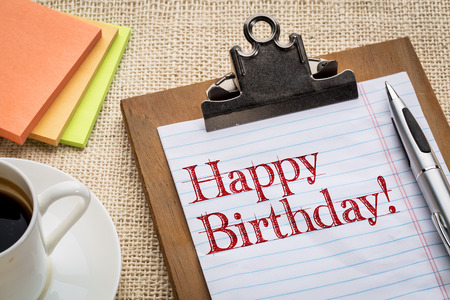 Happy Birthday on clipboard with a pen, coffee and sticky notes against burlap canvas - office celebration concept Stock Photo
