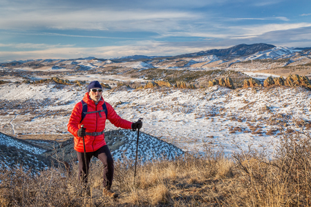 loveland: senior male hiker reaching top of a hill at foothills of Rocky Mountains - winter scenery at Devils Backbone Open Space near Loveland, Colorado
