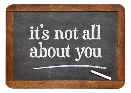 you: It is not all about you - a reminder in white chalk  on a vintage slate blackboard