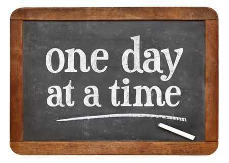 One day at a time  - white chalk text on a vintage slate blackboard Stock fotó
