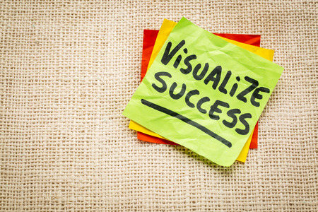 visualize success advice - handwriting on a sticky note against burlap canvas Imagens
