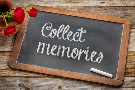 cobrar: Collect memories  - white chalk text on a vintage slate blackboard with red roses against rustic wood