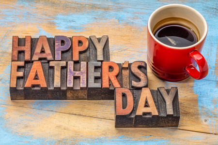 happy fathers day in vintage wood letterpress printing blocks with a cup of coffee