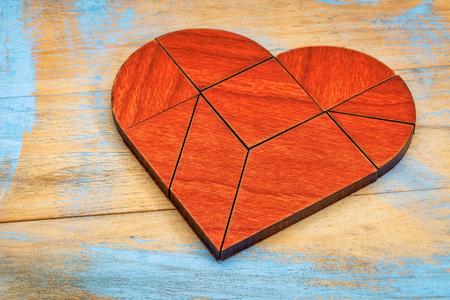 figuras abstractas: Versión corazón de tangram, un rompecabezas chino tradicional del juego hecha de diferentes partes de madera para construir figuras abstractas de ellos, el fondo de madera pintada