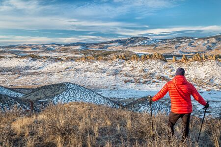 senior male hiker enjoying a view of rock formation at foothills of Rocky Mountains - winter scenery at Devils Backbone Open Space near Loveland, Colorado