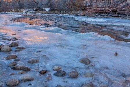 cache la poudre river: winter dusk over mountain river - partially froze Cache la Poudre River at Belvue near Fort Collins, Colorado