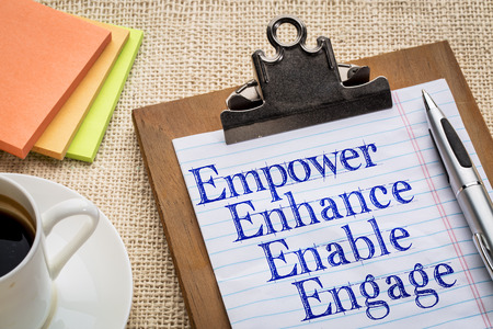 enable: motivational leadership, coaching or business concept - empower, enhance, enable and engage  words on a clipboard with a cup of coffee