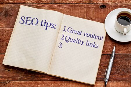 seo: SEO (search engine optimization) tips (great content and quality links) in an old notebook with a cup of coffee