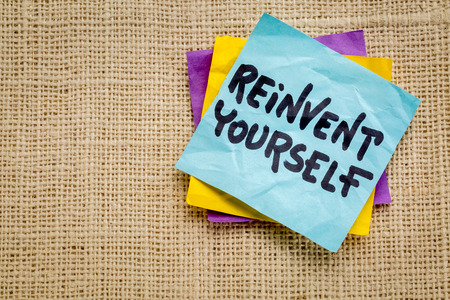 sackcloth: reinvent yourself advice - handwriting on a sticky note against burlap canvas Stock Photo