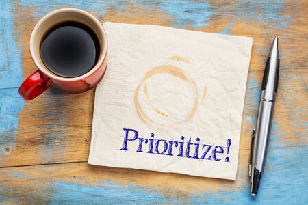 prioritize: prioritize - reminder or productivity concept on a napkin with a cup of coffee Stock Photo