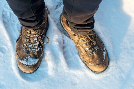 hiking boots: male hiker feet in old hiking boots on a snowy trail, top view