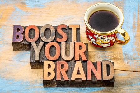 ブーストあなたのブランド - ビンテージ活版木材の種類、色インク、一杯のコーヒーで染色の隔離されたテキスト 写真素材