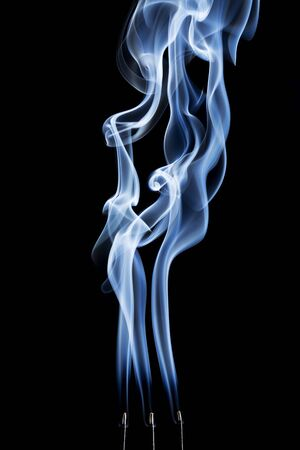 delicate smoke plumes, puffs and eddies  from  burning incense sticks