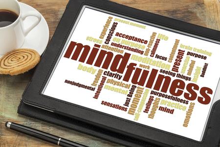 커피 한잔과 함께 grunge 나무 테이블에 대 한 디지털 태블릿에 mindfulness 단어 구름 스톡 콘텐츠