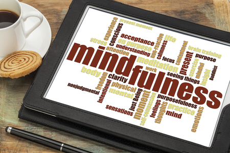 acceptance: mindfulness word cloud on a digital tablet against a grunge wood table with a cup of coffee